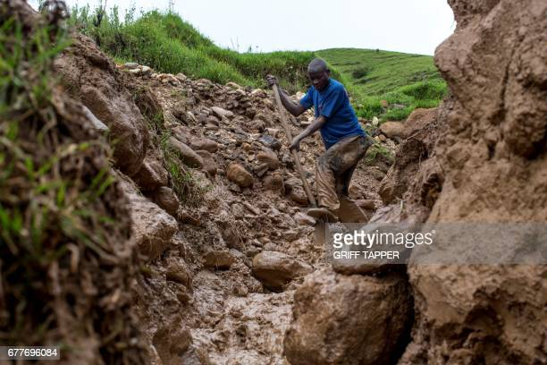 33yearold Salomon Kahizia digs in the runoff from an artisanal cassiterite and coltan mining site near Numbi in South Kivu eastern Democratic...