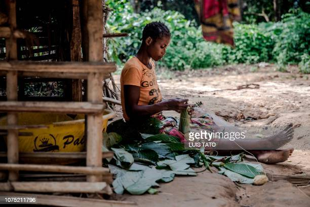 33yearsold Aimee Ngombo packs cassava bread to be sold in front of her house near the remote small village of Bonde Kongo Central Democratic Republic...
