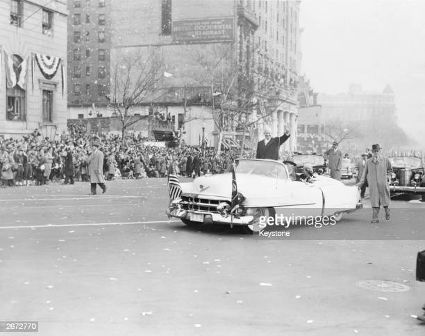 34th president of the United States Dwight David Eisenhower waves to the crowds, from his open-topped Cadillac Eldorado, after his Inauguration...
