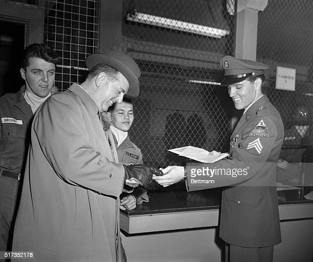 3/5/1960Fort Dix NJ After being discharged from the US Army today Elvis Presley grins as he hands his mustering out pay to his business manager...