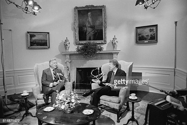 Washington, DC: President Carter chats with CBS anchorman Walter Cronkite as he prepares to answers telephone calls from Americans from around the...