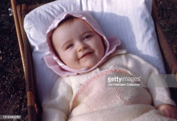35mm film photo shows a baby girl of approximately one year wearing a pink knit sweater and matching hat smiling from a cradle, which has been placed...