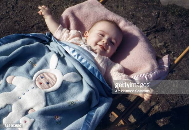 35mm film photo shows a baby girl of approximately one year wrapped in a blue bunny-themed blanket as she smiles and extends her arms out from her...