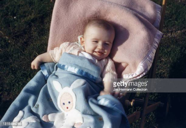35mm film photo shows a baby girl of approximately one year wrapped in a blue bunny-themed blanket as she smiles from her stroller, 1944.