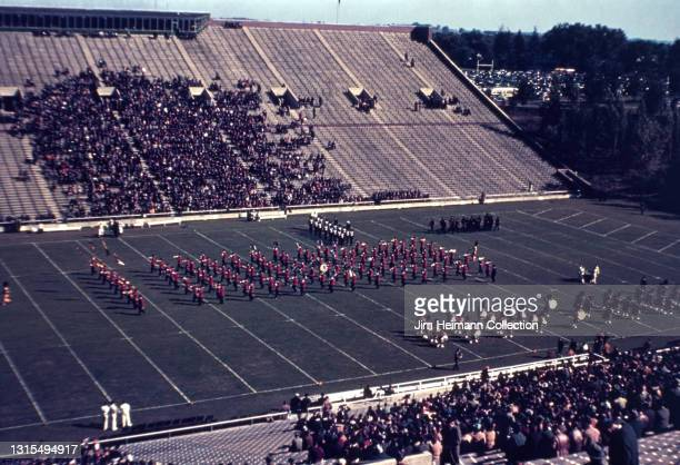 35mm film photo shows a bleacher level view of a football game at Iowa Stadium. It is halftime and a marching band is performing in the center of the...