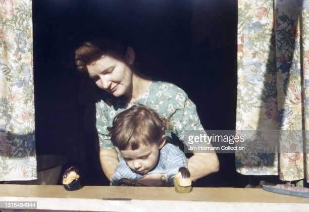 35mm film photo shows a mother and son standing at a window ledge. The boy is looking down at his lap as his mom helps him with something, 1944.