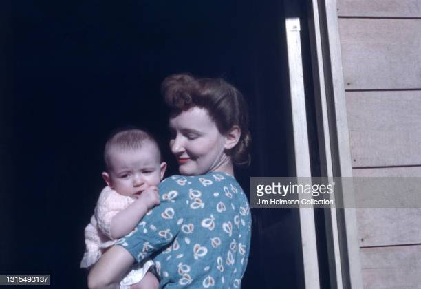 35mm film photo shows a mother standing in a doorway with a child in her arms. She gazes lovingly at the infant, which is busy sucking his thumb,...