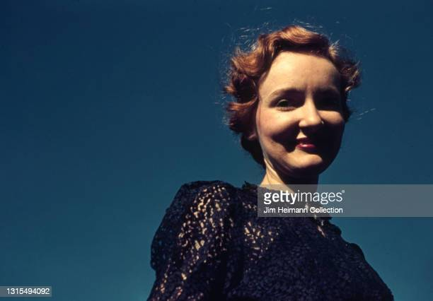 35mm film photo shows a waist-level portrait of the photographer's wife. She wears a navy-colored blouse and smiles against the backdrop of a bright...