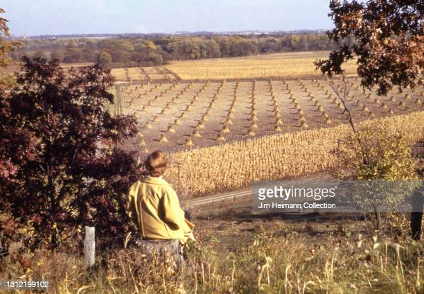 35mm film photo shows a woman looking out onto a hay field in Iowa City, 1940.