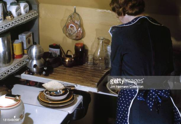 35mm film photo shows a woman standing with her back to us at the kitchen sink of her suburban Washington home. She wears a polkadot apron as she...