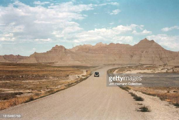 35mm film photo shows an automobile making its way down an empty dirt road in Badlands National Park. In the background, we see the layered rock...
