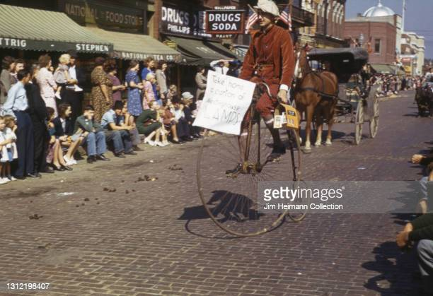 35mm film photo shows the Festicorn Parade in Iowa City. A man rides a penny-farthing with a sign advertising lamps; behind him, a horse-drawn buggy...