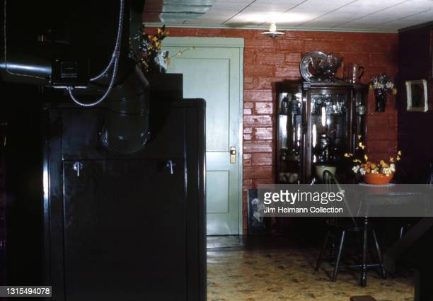 35mm film photo shows the furnace room in a house in Washington state. In one corner is the furnace, while on the other side of the room is a small...