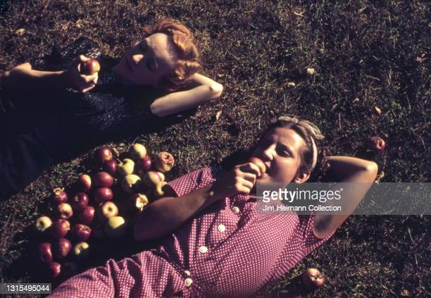 35mm film photo shows two women lying on a patch of grass near an apple orchard in Virginia, 1939.