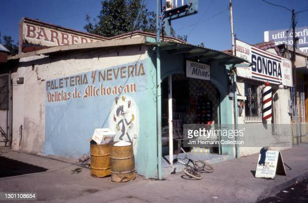 35mm photo shows a retail section of Tecate, Mexico where an ice cream store and a barbershop are open for business, 1992.