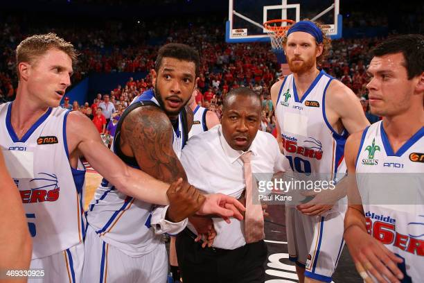 36ers players hold back coach Joey Wright after a post game melee during the round 18 NBL match between the Perth Wildcats and the Adelaide 36ers at...