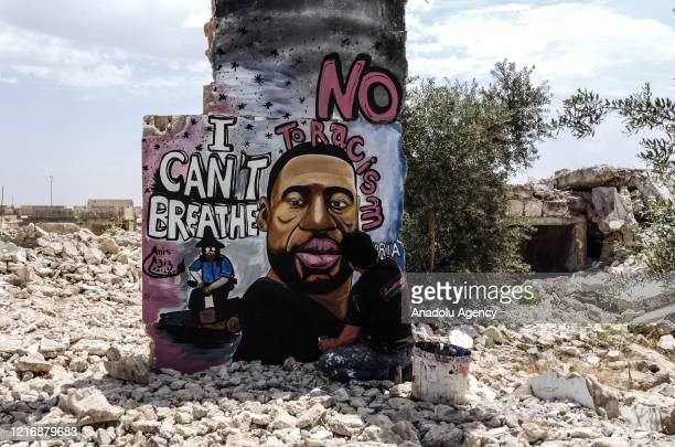 A 36year old graffiti artist Aziz Asmar paints a mural depicting of George Floyd an unarmed black man who died after being pinned down by a white...