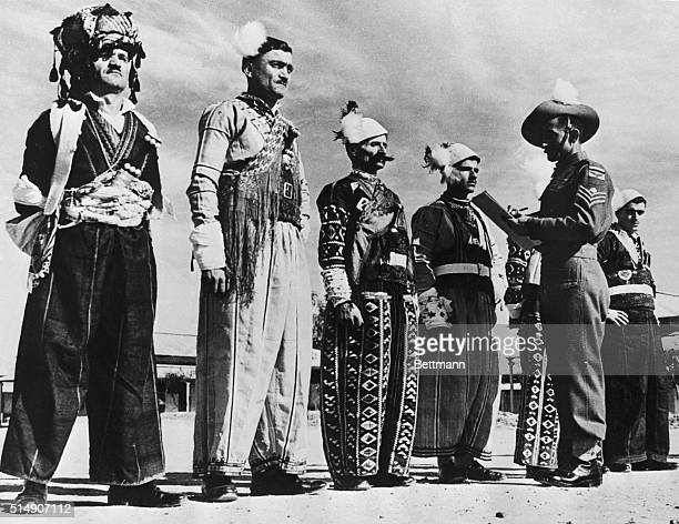 3/8/1944Baghdad Iraq A group of native Iraq tribesmen dressed in their picturesque tribal costumes are shown being checked out by an officer before...