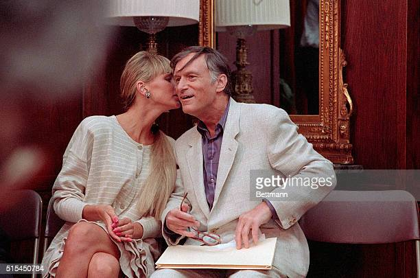3/9/1988Los Angeles California Playboy magazine publisher Hugh Hefner receives a peck on the cheek from his latest livein girlfriend Kimberly Conrad...