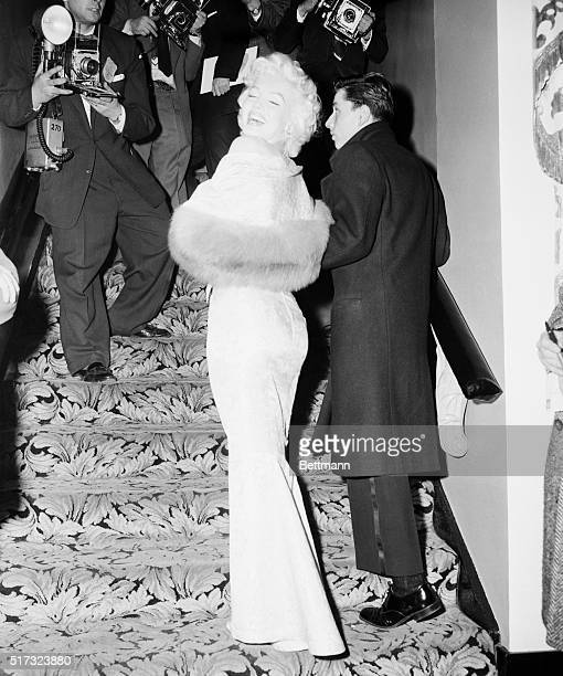 New York: Clad in a tightly-fitted gown, Marilyn Monroe glances over her shoulders on arriving at the Astor Theatre tonight for the benefit premiere...