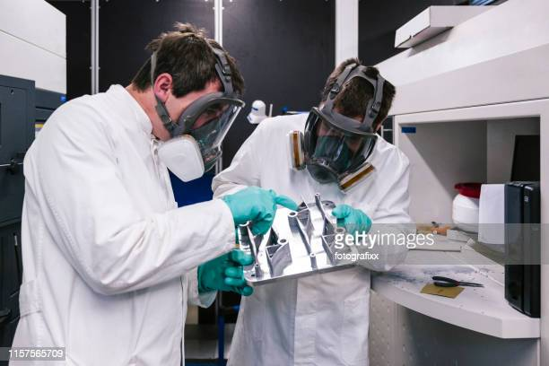 3d printing: two scientists work on a slm machine (selective laser melting) for metal - 3d printing stock pictures, royalty-free photos & images