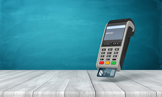 3d rendering of point-of-sale terminal suspended in air above wooden table near blue wall with copy space. 1182643190