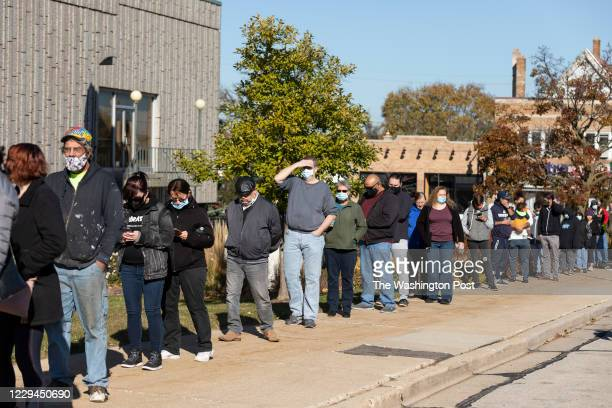 3rd: A line of voters wrap around the sidwalks outside West Allis City Hall, a suburb just to the west of Milwaukee on November 3rd, 2020. Voters...