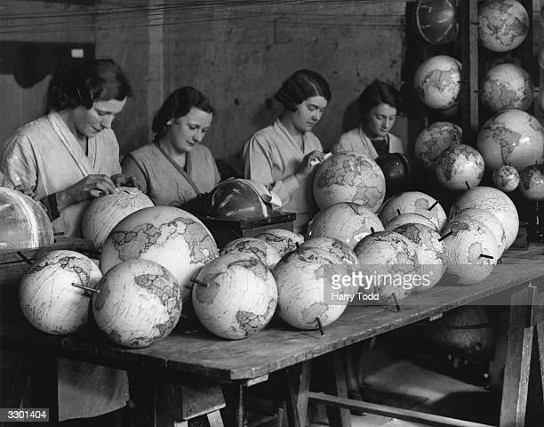 Women workers attaching strips of map to globes at the Geographia Factory in London