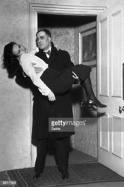 Godfrey Tearle carries an unconscious Antoinette Collier in his arms in a scene from the play 'Sixteen' at the Criterion Theatre