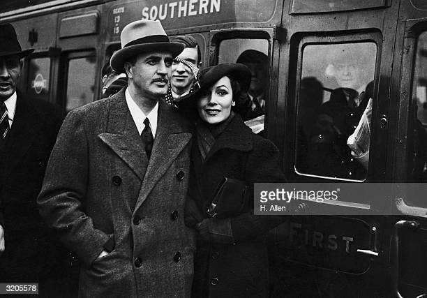Hollywood film star, Dolores Del Rio arriving at Waterloo station in London with her husband, MGM art director and designer of the Oscar trophy,...