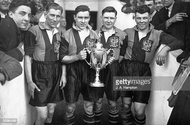 Dulwich Hamlet FC football players hold the FA Amateur Cup at Upton Park London Left to right C Murray H Robbins L Morrish and A Hugo