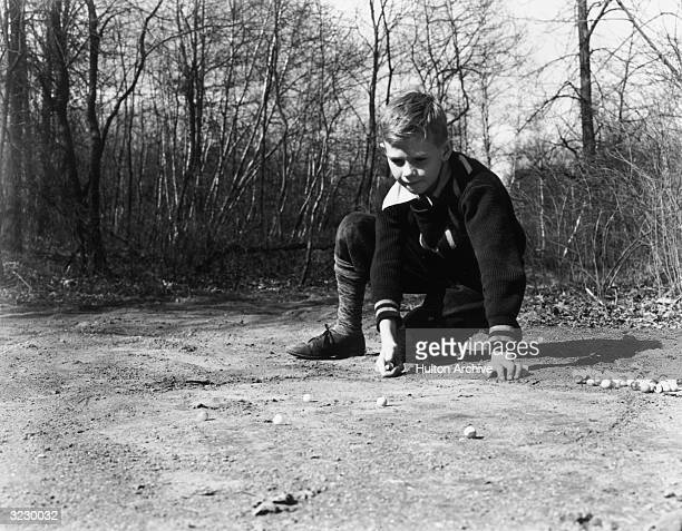 A boy kneels on the ground in front of woods playing marbles