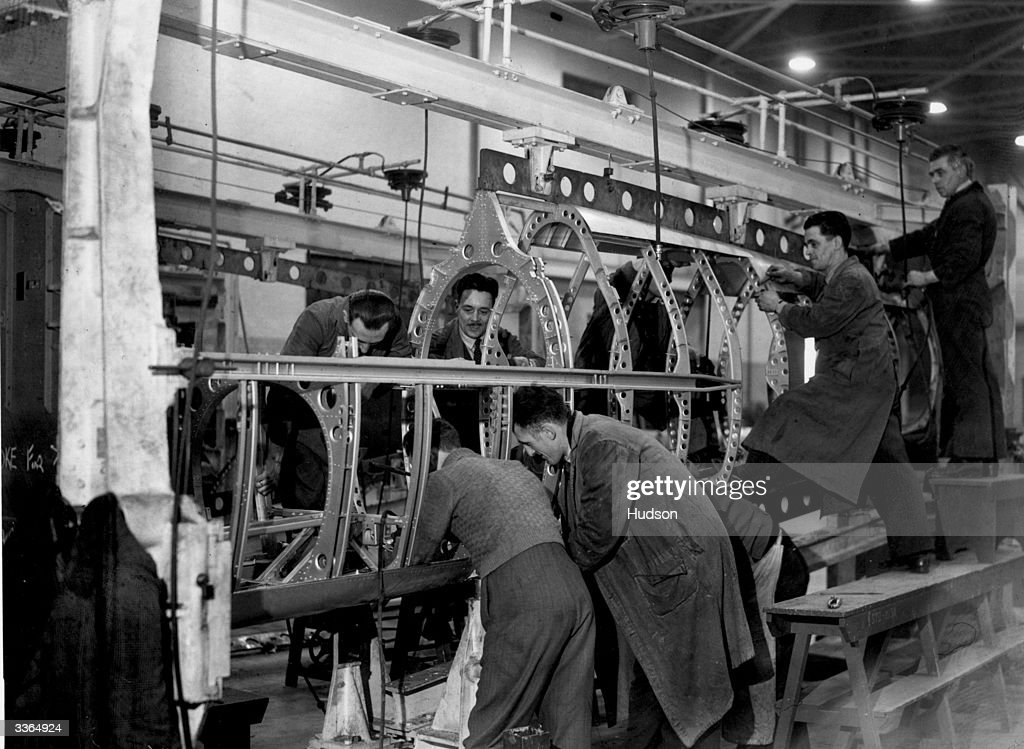 Workmen employed in the construction of a spitfire fuselage in the 'stocks' at a Midlands aircraft factory.