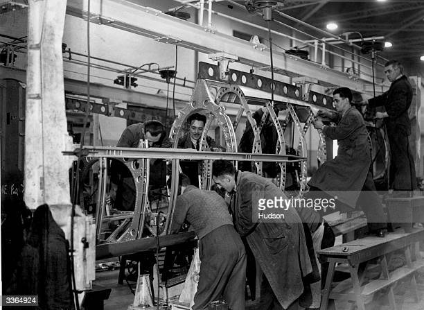 Workmen employed in the construction of a spitfire fuselage in the 'stocks' at a Midlands aircraft factory