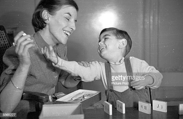 Mother playing with her young son, who was born deaf. By shaping her words clearly he learns to distinguish words; by copying the shapes himself, he...