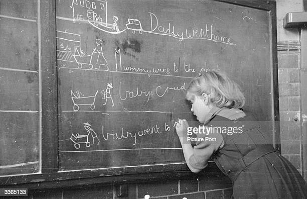 Young pupil writing on the blackboard at a school which specialises in teaching deaf children. The drawings beside the word prove that she...