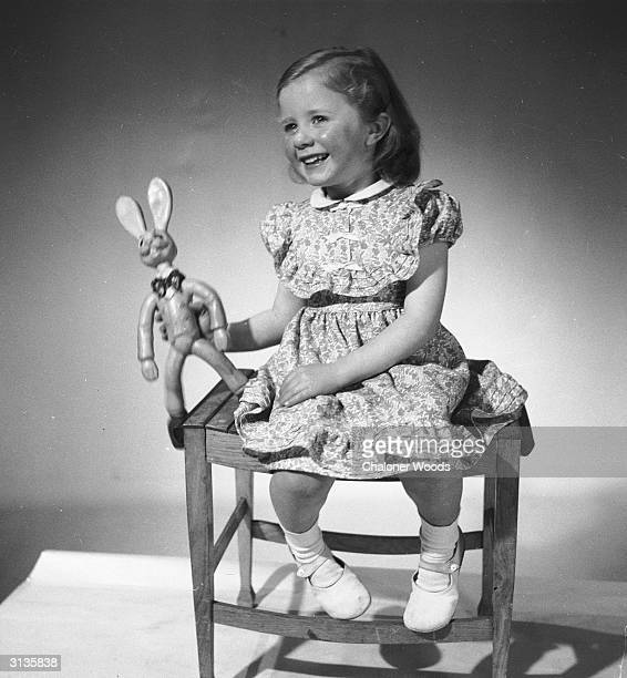 A little girl models a floral print dress with puffed sleeves and tucks round the yoke and hem from Viyella Children's fashions