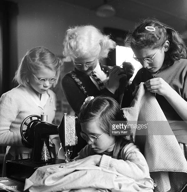 Pupils at a school for partially-sighted children concentrate during a needlework class.
