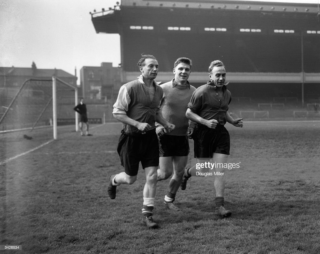 Three England players running around the track at Highbury during a training session for their forthcoming match against Scotland. Left to right: Stanley Matthews, Duncan Edwards and captain Billy Wright.