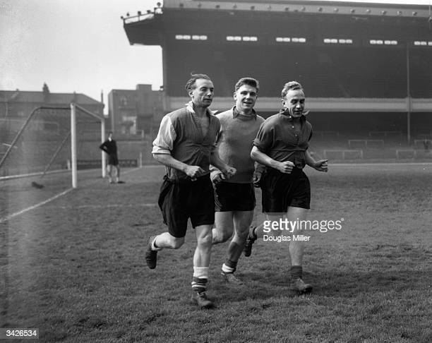 Three England players running around the track at Highbury during a training session for their forthcoming match against Scotland. Left to right:...