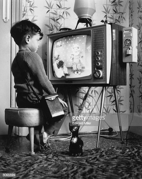 Little boy watches 'Andy Pandy' at home on a pay television. A slot meter on the right allows him to insert 6d coins per hour of viewing.