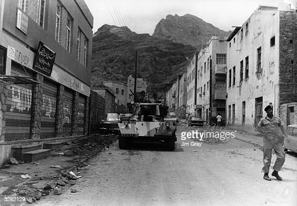 A squadron of British soldiers patrol a street in riottorn Aden during talks on the future of the South Arabian Federation