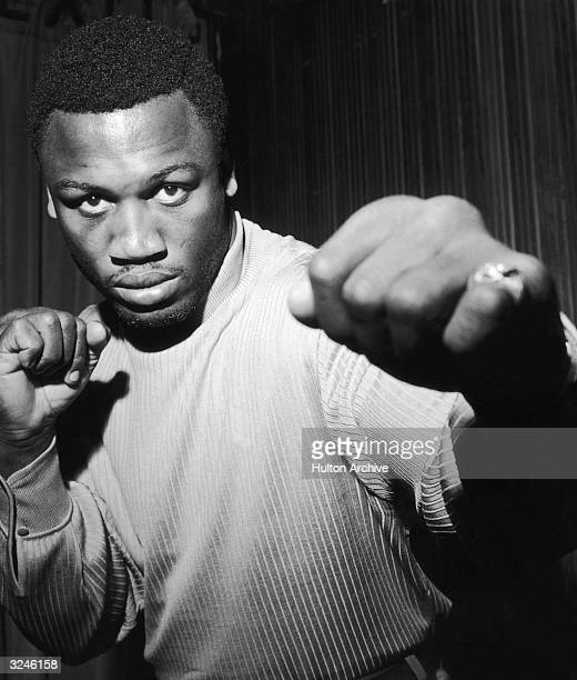 Promotional portrait of American heavyweight boxer Joe Frazier wearing a sweater and posing in a fighting stance London England