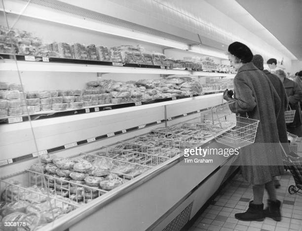 Shoppers look at foodstuffs on show in refrigerated cabinets at the newlyopened Sainsbury's supermarket at Sutton Surrey
