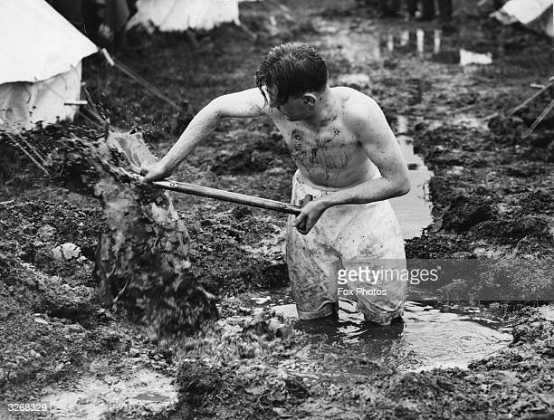 A soldier strips to his underwear while digging a channel to help drain flood water