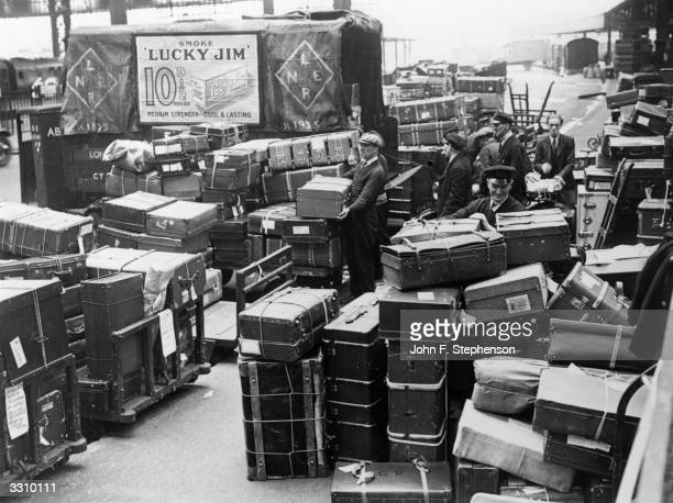 Men loading suitcases at Waterloo Station in London In the background is an advertisement for 'Lucky Jim' cigarettes
