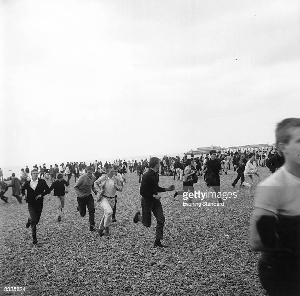A group of Mods running along the beach at Hastings Kent during violence between Mods and Rockers