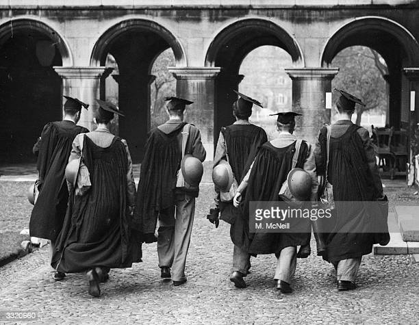 At Emmanuel College, Cambridge undergraduate members of the University fire squad in cap and gown, are carrying their gas masks and tin helmets so as...