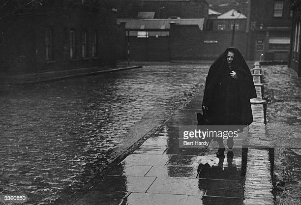 A woman walking along a street in Wapping East London during heavy rain Original Publication Picture Post 4931 The Pool Of London pub 1949