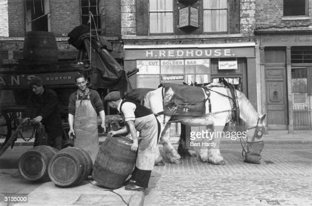 Men unloading barrels of beer outside a pub in the Pool of London Original Publication Picture Post 4931 The Pool Of London pub 1949